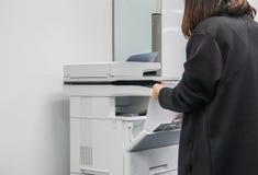 在女实业家的选择聚焦黑夹克的放纸板料入复制的商业文件的办公用打印机盘子 免版税库存照片