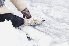 在女性冰鞋鞋子的腿在冰说谎 图库摄影