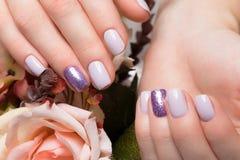 在女性手上的紫色整洁的修指甲在花背景 钉子设计 库存照片