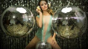 在女用贴身内衣裤的性感的迪斯科妇女跳舞有discoballs的 库存图片