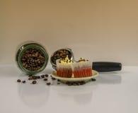 在奶油色茶碟的两个松饼在背景中溢出了咖啡bea 图库摄影