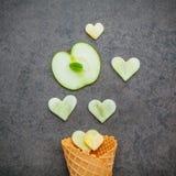 在奶蛋烘饼苹果锥体和心脏形状的苹果计算机切片在da设定了 库存图片