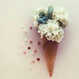 在奶蛋烘饼锥体的冰淇凌的模仿装饰了薄荷叶 八仙花属在与薄荷叶的奶蛋烘饼锥体开花 图库摄影