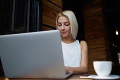在她便携式的网书的年轻迷人的女性键盘输入文本,使用技术的华美的欧洲妇女 免版税库存照片