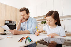 在她工作的父亲旁边的女孩图画 免版税图库摄影
