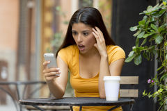 在她巧妙的电话冲击的可爱的拉丁妇女 免版税图库摄影