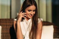 在她期间的一台膝上型计算机在电话谈话的年轻美好的女孩用途 蝴蝶日草夏天晴朗的swallowtail 免版税库存照片
