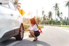 在她残破的汽车的女商人司机改变的轮胎 免版税图库摄影