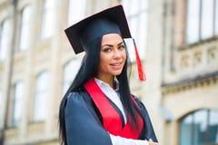 在她毕业典礼举行日微笑的愉快的妇女画象 免版税库存照片