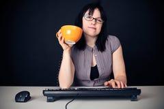在她的个人计算机前面的少妇 库存图片