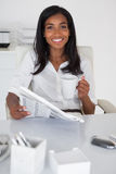 在她的书桌的俏丽的女实业家读书报纸 库存图片