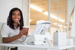 在她的书桌的俏丽的女实业家读书报纸 库存照片