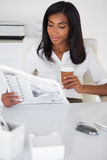在她的书桌的俏丽的女实业家读书报纸 免版税库存图片