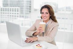 在她的书桌的女实业家饮用的咖啡使用微笑对照相机的膝上型计算机 库存照片