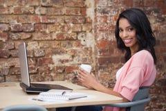 在她的书桌的微笑的妇女饮用的咖啡使用膝上型计算机 库存图片