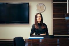 在她的书桌问候顾客前面的接待员妇女 免版税库存图片