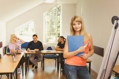 在她的伙伴前面的学生女孩在教室 免版税库存图片