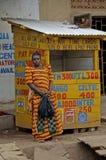 在她的卖电话卡片的商店前面的五颜六色的妇女为 库存图片