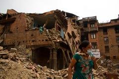 在她的地震之外的一名妇女在Bhaktapur, Ne现在破坏了房子 免版税图库摄影