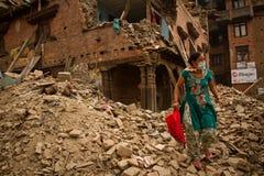 在她的地震之外的一名妇女在Bhaktapur, Ne现在破坏了房子 免版税库存图片