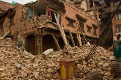 在她的地震之外的一名妇女在Bhaktapur, Ne现在破坏了房子 库存照片