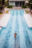 在她的夏天期间,一个诱人的性感的模型的顶视图空中照片在白色游泳衣的在旅馆水池享用放松 免版税库存图片