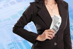 在她的夹克里面的女商人掩藏的金钱 免版税库存图片