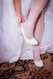 在她的婚礼之日的新娘贴合鞋子 免版税库存照片