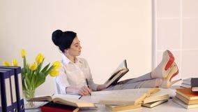 在她的工作场所的女性开会和笑,当读拿着书时 股票视频