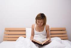 在她的年轻美丽的妇女阅读书床 库存照片