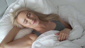 在她的床上的微笑的白肤金发的妇女在明亮的卧室在被子下 股票视频