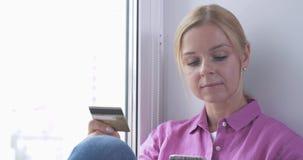 在她的手上的微笑的妇女画象拿着信用卡,当在网上时购物 股票录像