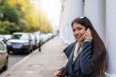 在她的手机的妇女谈话在一条经典伦敦街道上 库存图片
