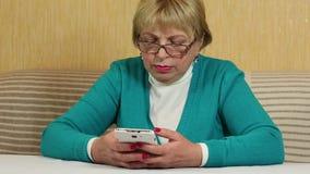 在她的手机的妇女键入的sms 有白色智能手机的妇女 股票录像