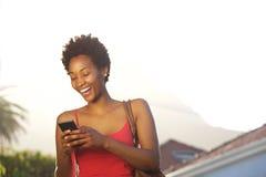 在她的手机的微笑的年轻非洲读书正文消息 免版税库存图片