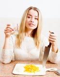 在她的手&有上乐趣饮用的饮料美丽的白肤金发的少妇拿着一把刀子有嫉妒放松的 免版税库存图片