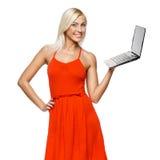 在她的掌上型计算机的愉快的妇女藏品膝上型计算机 免版税库存图片