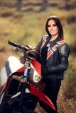 在她的摩托车旁边的女性摩托车越野赛竟赛者 免版税库存照片