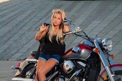 在她的摩托车的性感的白肤金发的开会 免版税库存照片