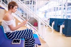 在她的智能手机的创造性的女性设计师传讯,当坐时 库存图片