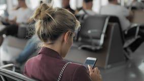 在她的智能手机的未被认出的年轻女性用途人脉,当等待飞行时,当坐在机场时 股票录像