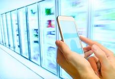 在她的智能手机的购物单在超级市场 免版税库存照片
