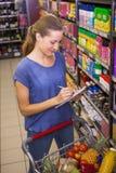 在她的杂货名单上的俏丽的妇女文字 免版税库存照片