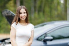 在她的汽车打破的汽车前面的妇女 免版税库存图片