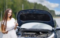 在她的汽车打破的汽车前面的妇女 库存图片