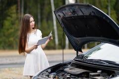 在她的汽车打破的汽车前面的妇女 免版税图库摄影