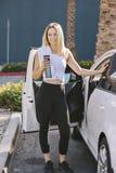 在她的汽车的适合的年轻白肤金发的女孩立场用水Bottile在她的手上在锻炼以后 免版税库存照片