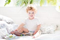 读在她的父母的愉快的滑稽的婴孩一本书供住宿 库存图片