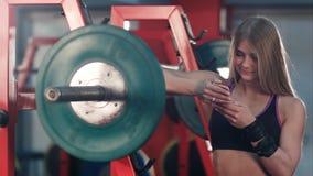 在她的电话的微笑的运动妇女传讯在健身房 库存照片