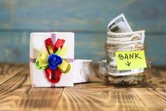 在她的硬币,玩具汽车,礼物盒的一个玻璃瓶子 概念在银行中做储蓄并且获得奖 那里定调子 免版税图库摄影